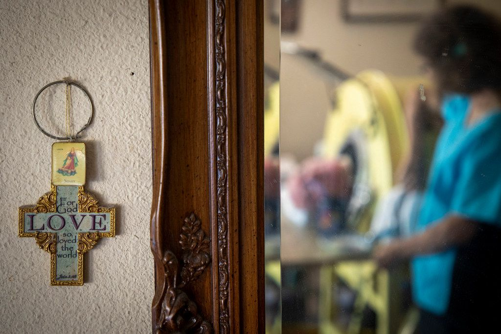 Paul Alexander is reflected in a mirror as he chats with caregiver and friend Kathryn Gaines from his iron lung at his home in Dallas.
