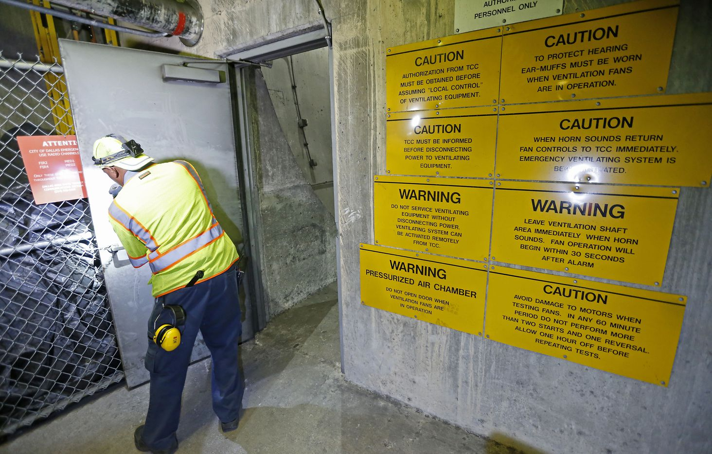 Warning signs about as mechanic Amos Hargrove opens a door to the fan room inside the DART's underground tunnel in Dallas, Friday, July 20, 2018.