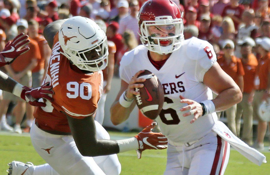 FILE - Oklahoma quarterback Baker Mayfield (6) looks for a receiver as he avoids Texas defensive lineman Charles Omenihu (90) during the Red River Showdown at the Cotton Bowl in Dallas on Saturday, Oct. 14, 2017. (Louis DeLuca/The Dallas Morning News)