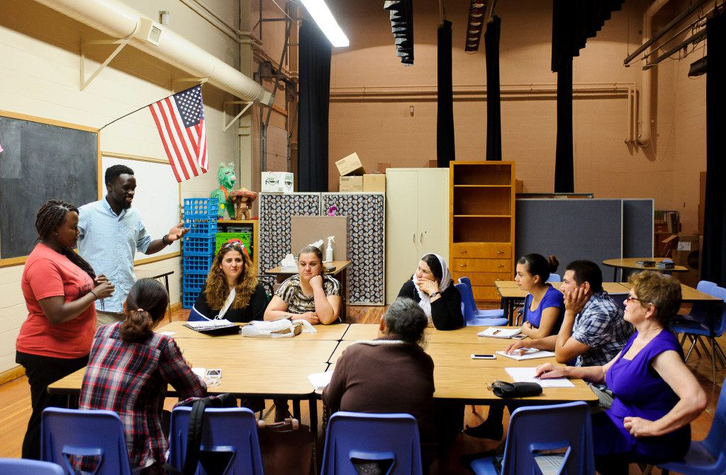 In a classroom located backstage of an auditorium, volunteer tutors Kezie Mwaniki (far left) and Daniel Otto (left) speak to their class including people from Iraq, Mexico, Ukraine, Ethiopia and China during a Lincoln Literacy class at Culler Middle School in Lincoln, Neb. on Wednesday, July 12, 2017. Lincoln Literacy is a nonprofit formed to teach the English language to immigrants and refugees arriving in Lincoln. (Matt Ryerson/Special Contributor)