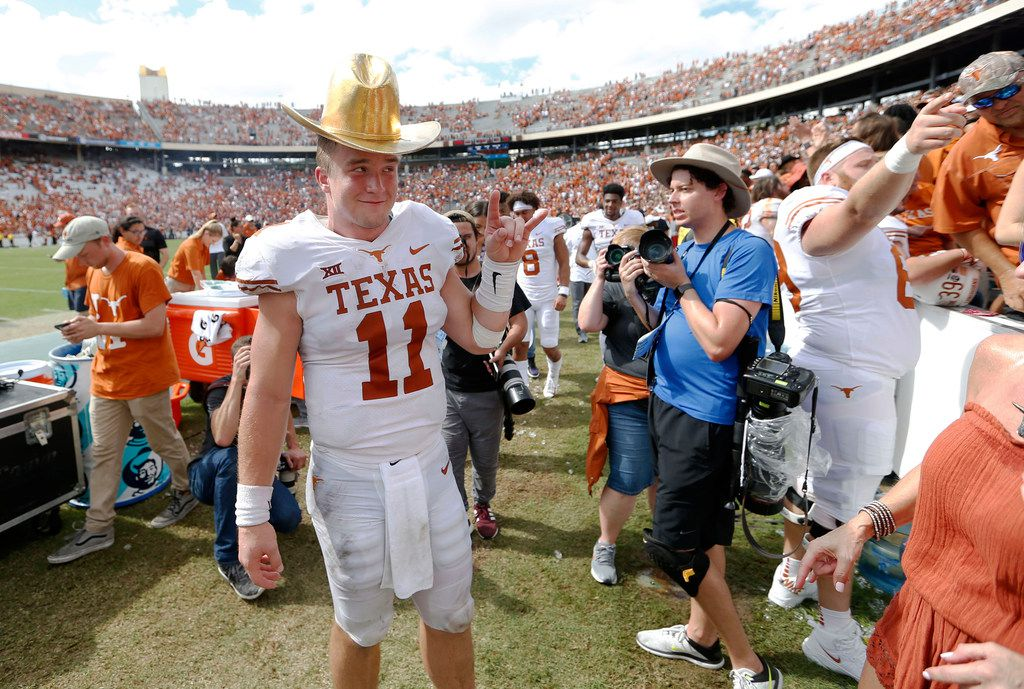 Texas quarterback Sam Ehlinger (11) wears the golden hat as he poses for photos for his family after defeating Oklahoma, 48-45, at the Cotton Bowl in Dallas on Saturday, Oct. 6, 2018. (Vernon Bryant/Dallas Morning News/TNS)