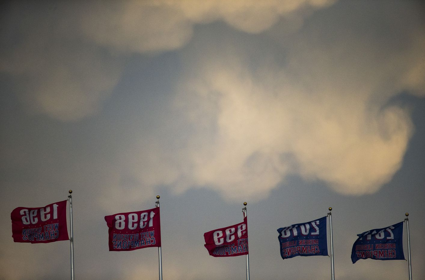 Storm clouds roll in over division championship flags between the second and third innings of an MLB game between the Texas Rangers and the Kansas City Royals on Friday, April 21, 2017 at Globe Life Park in Arlington, Texas.