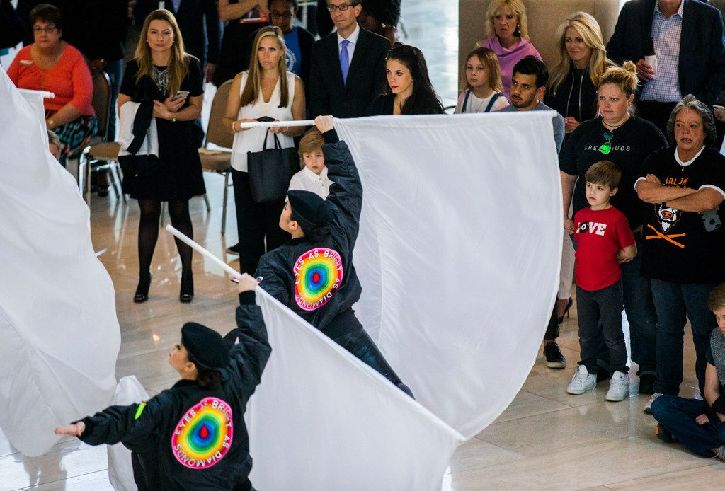 """People watch as the Haltom color guard performs during a pop-up performance entitled """"Eyes as Bright as Diamonds"""" to kick off the Soluna International Music & Arts Festival on Wednesday, April 11, 2018 at the Morton H. Meyerson Symphony Center in Dallas. The performance brings together New York artist Jen Ray, musician Sarah Jaffe and several Dallas performers. (Ashley Landis/The Dallas Morning News)"""