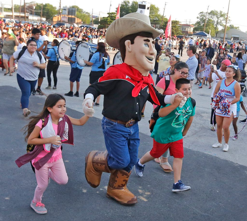"""State Fair of Texas mascot """"Little Big Tex"""" escorts two students into the Dallas Mayor's Back to School Fair held at the Centennial Building at Fair Park in Dallas on Friday, Aug. 3, 2018."""