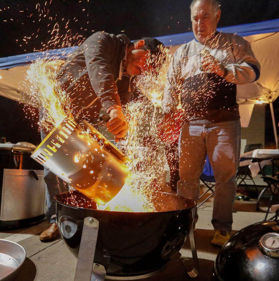 Jacob Sullum and Donny Swartz pour heated coals into the team's smoker at the  Dallas Kosher BBQ Championship.