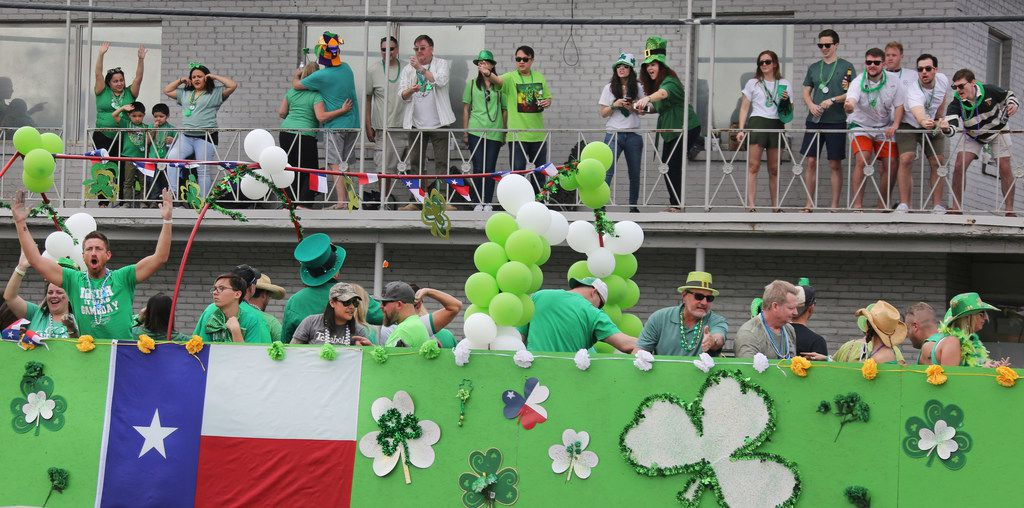 Spectators get a perfect vantage point to view a passing float during the Dallas St. Patrick's Parade & Festival along Greenville Avenue in Dallas on Saturday.
