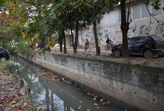 Un canal de agua contaminada recorre la favela Ciudad de Dios.