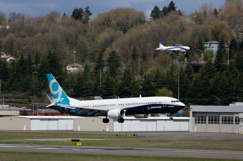 """(FILES) This file photo taken on April 13, 2017 shows a chase plane and Boeing 737 MAX 9 land during a first-flight event for the company's new airplane at Boeing Field in Seattle, Washington.   Boeing plans to cut hundreds of additional jobs in its civil aviation business due to slowing sales, a spokesman said on April 17, 2017. """"In an ongoing effort to increase overall competitiveness and invest in our future, we are reducing costs and matching employment levels to business and market requirements,"""" Boeing spokesman Doug Alder said.  / AFP PHOTO / Jason RedmondJASON REDMOND/AFP/Getty Images"""