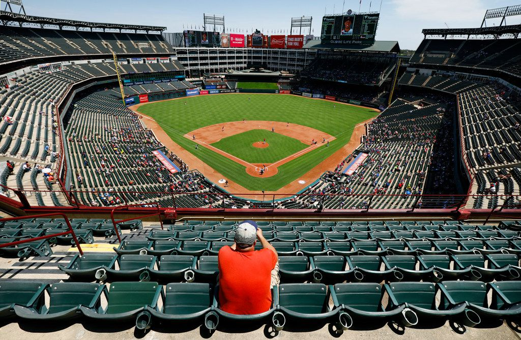 A lone baseball fan, who wished not to provide his name, had several sections of seats in the sun to choose from during the Texas Rangers-Cleveland Indians game at Globe Life Park in Arlington, Texas, Sunday, July 22, 2018.  By the end of the game the temperature was 108¼, one of the hottest games on record. (Tom Fox/The Dallas Morning News)