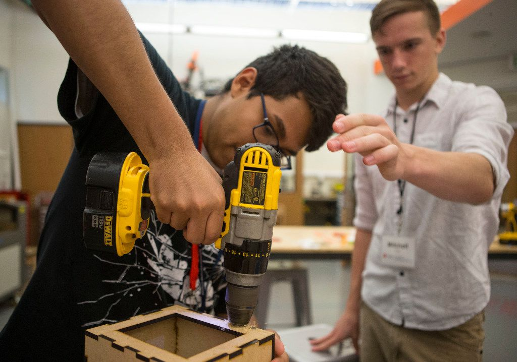 Elias Galarza, 17, of Dallas drills a hole for a hinge under the guidance of instructor Mitchell Dye, a Lyle Engineering Student at SMU, during an engineering summer camp at the Deason Innovation Gym in Caruth Hall at SMU on June 29, 2017.