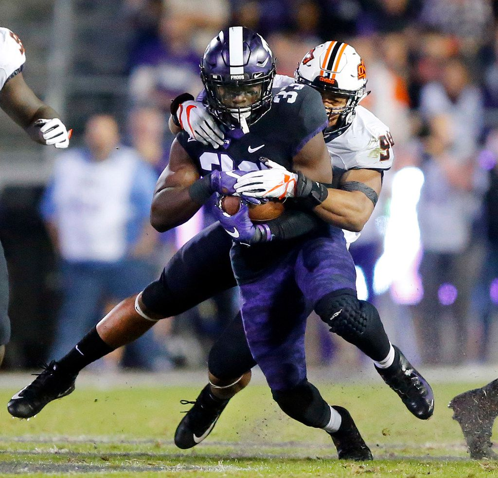 FILE - Oklahoma State Cowboys defensive end Jordan Brailford (94) makes a diving tackle of TCU Horned Frogs running back Sewo Olonilua (33) during the second quarter at Amon G. Carter Stadium in Fort Worth, Texas, Saturday, November 24, 2018. (Tom Fox/The Dallas Morning News)