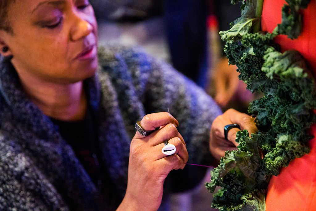 Designer Josette Golatt (left) sews lettuce on to the dress of model Dr. Candace Freeman before the Greater Dallas Restaurant Association's Food in Fashion event on Wednesday, Feb. 7, 2018, at Trinity Groves in Dallas. (Ashley Landis/The Dallas Morning News)