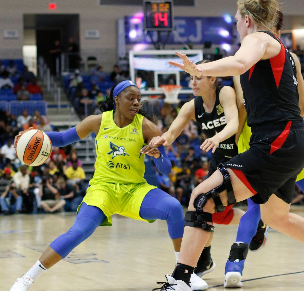 Dallas Wings guard Arike Ogunbowale (24) maneuvers through the defense of Las Vegas guard Kelsey Plum (10), center, and center Carolyn Swords (4) during first half action. The two teams played their WNBA game at College Park Center in Arlington on August 3, 2019. (Steve Hamm/ Special Contributor)