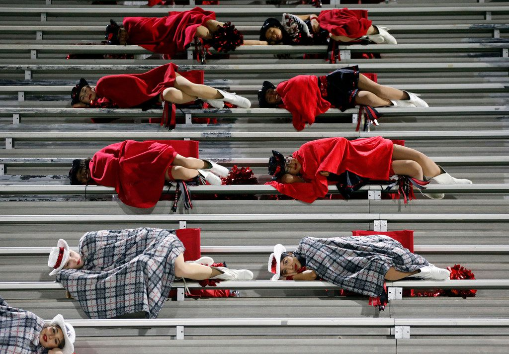Members of Hillcrest High Panaders drill team feign sleep, while North Dallas High has the ball on offense, during the first half of their high school football game at Franklin Stadium in Dallas on Friday, October 11, 2019. (John F. Rhodes / Special Contributor)