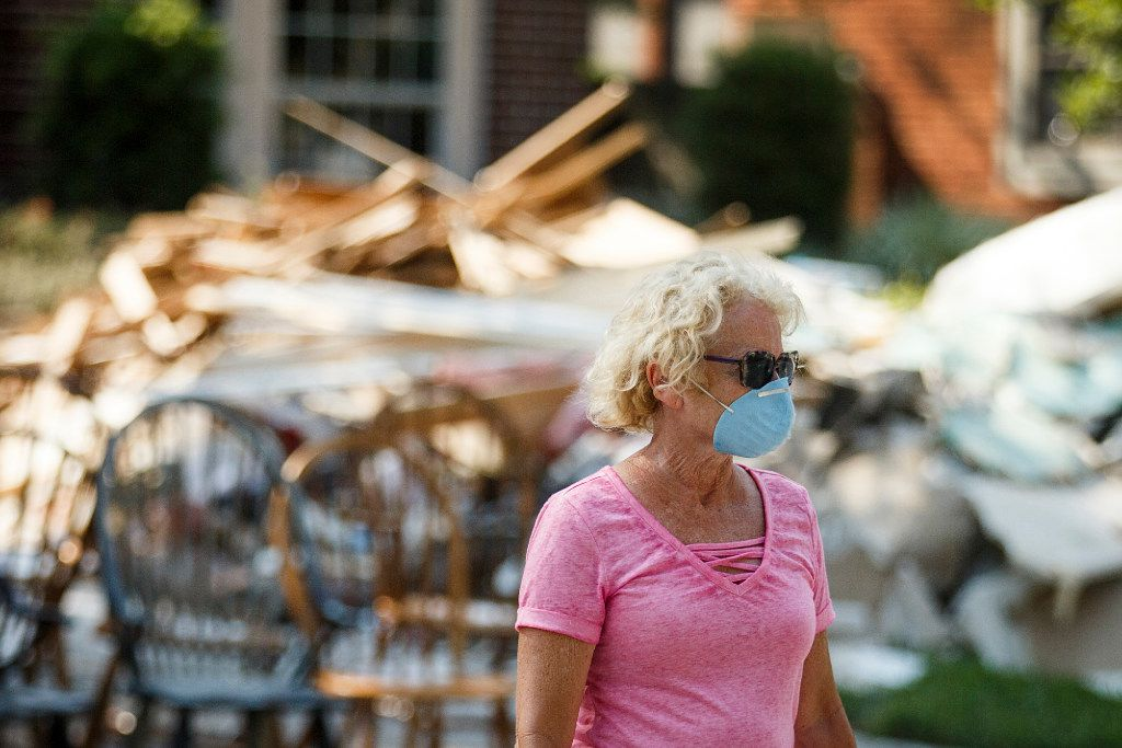 Sherry Young wears a protective mask as she walks across the street past the pile of rubble in front of her home which was damaged by flooding from Hurricane Harvey in the Fosters Mill Village subdivision of the Kingwood neighborhood on Monday, Sept. 4, 2017, in Houston.