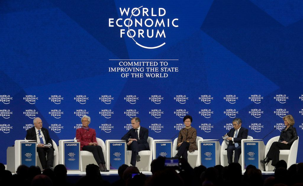 From left, Martin Wolf, associate editor and chief economics commentator of the Financial Times newspaper; Christine Lagarde, managing director of the International Monetary Fund;  Mark Carney, governor of the Bank of England; Carrie Lam, chief executive of Hong Kong SAR; Haruhiko Kuroda, governor of the Bank of Japan; and Callahan Erdoes, CEO asset and wealth management of JPMorgan Chase & Co., attend a discussion during the annual meeting of the World Economic Forum in Davos, Switzerland on Jan. 26, 2018. (AP Photo/Markus Schreiber)