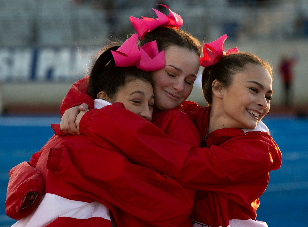 Parish Episcopal varsity cheerleader (from left) Izzi Baggett, Hope Brown and Sami Pong embrace to keep each other warm before the football game between Parish Episcopal High School and Bishop Dunne Catholic School at the Gloria H. Snyder Stadium in Farmers Branch, Texas, on Friday, Oct. 11, 2019. (Lynda M. Gonzalez/The Dallas Morning News)