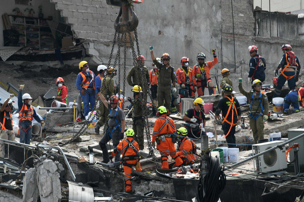 Rescue workers ask for silence during the search of survivors in a building at Colonia Roma in Mexico City on Sept. 23, 2017, four days after the powerful quake that hit central Mexico.