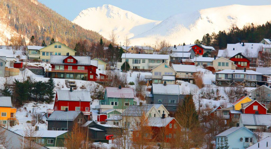 Bright houses like these are common in Norway and viewed en masse from cruise ships such as the Hurtigruten vessels.