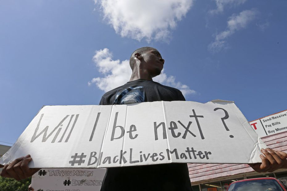Niamke Ledbetter, of Oak Cliff, Texas, holds a sign at a Black Lives Matter protest on Park Lane in Dallas on Sunday, July 10, 2016.