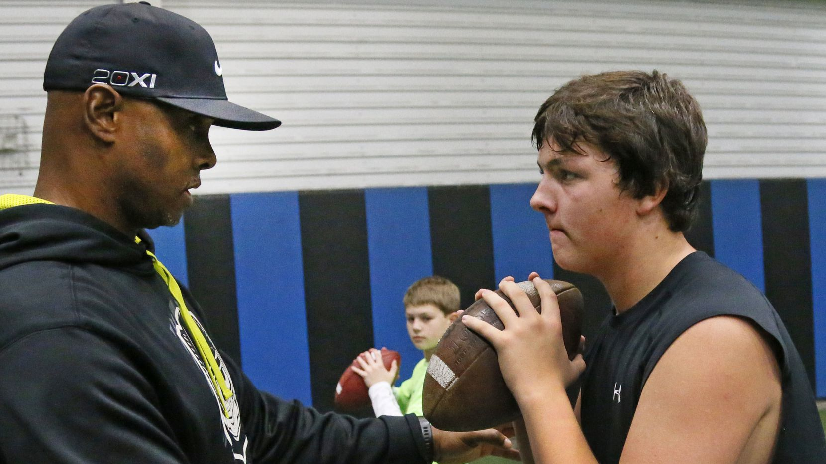 Former Texas A&M quarterback Kevin Murray works as a quarterbacks coach with 16-year-old Zach Gibson, right, and 11-year-old Dylan Gibson at Plano West High School in Plano.
