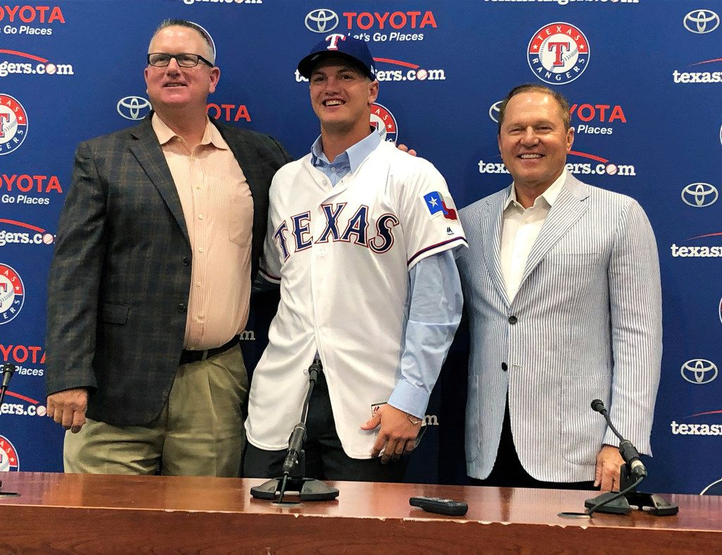 Texas Rangers senior director of amateur scouting Kip Fagg; Josh Jung, the baseball team's first-round draft pick; and Jung's agent, Scott Boras, right, pose for photos after a news conference before a baseball game between the Rangers and Los Angeles Angels in Arlington, Texas, Wednesday, July 3, 2019. (AP Photo/Schuyler Dixon)