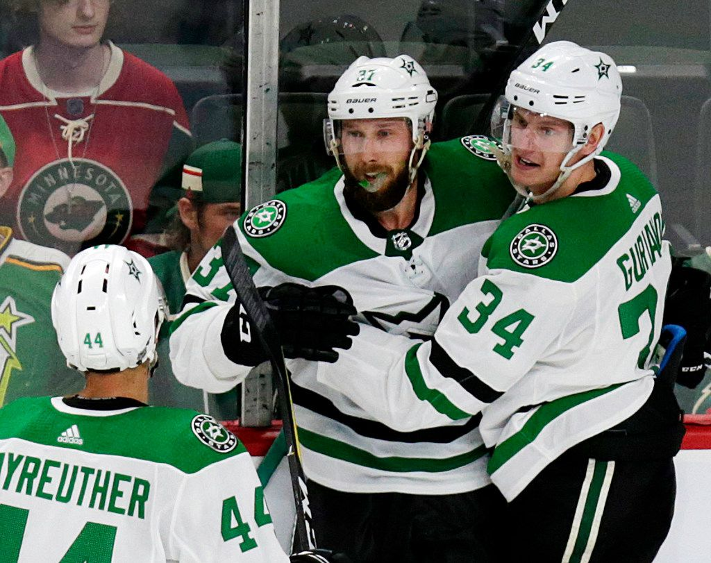 Dallas Stars center Justin Dowling (37) celebrates with teammates Denis Gurianov (34) and Gavin Bayreuther after scoring  against the Minnesota Wild during the third period of a preseason NHL hockey game Thursday, Sept. 20, 2018, in St. Paul, Minn. The Stars defeated the Wild 3-1. (AP Photo/Andy Clayton-King)