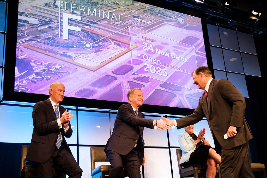 Dallas Mayor Mike Rawlings (right) shakes hands with American Airlines CEO Doug Parker (center) as DFW Airport CEO Sean Donohue (left) and Fort Worth Mayor Betsy Price applaud after it was announced that the airport would be adding a new terminal during the annual state of the airport address at the Hyatt Regency DFW on Monday, May 20, 2019..