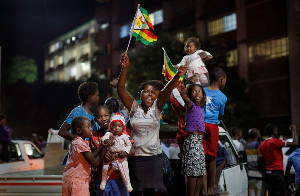 Zimbabweans celebrate at night at an intersection in downtown Harare, Zimbabwe Tuesday, Nov. 21, 2017. Robert Mugabe resigned as president with immediate effect Tuesday after 37 years in power, shortly after parliament began impeachment proceedings against him.