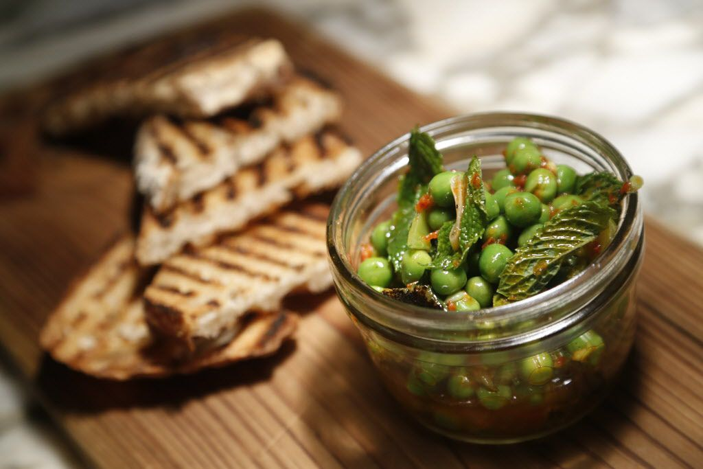 Spicy oil-cured peas at CBD Provisions in the Joule Hotel is served with house-made sourdough toast.