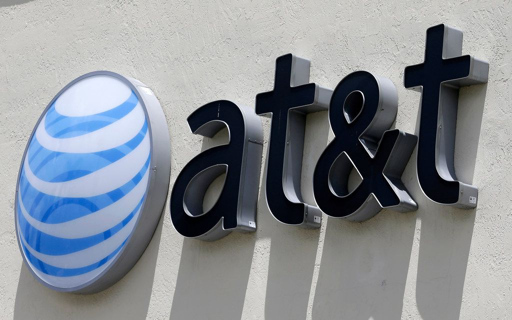 FILE - This Thursday, July 27, 2017, file photo shows an AT&T logo at a store in Hialeah, Fla. Dozens of companies, including AT&T, have announced they are giving their employees bonuses, following the passage of the Republican tax plan that President Donald Trump signed into law in December. (AP Photo/Alan Diaz, File)