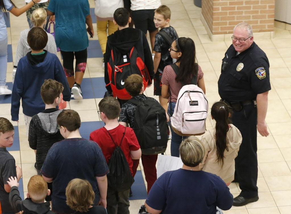 El policía Chris Golden sonríe a los estudiantes que llegan a la cafetería de la secundaria Scott Johnson en McKinney. VERNON BRYANT/DMN