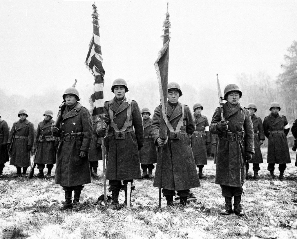 Two color guards and color bearers of the Japanese-American 442nd Combat team stand at attention while their citations are read somewhere in France during World War II on Nov. 12, 1944 .  They  are standing on the ground where many of their comrades fell.