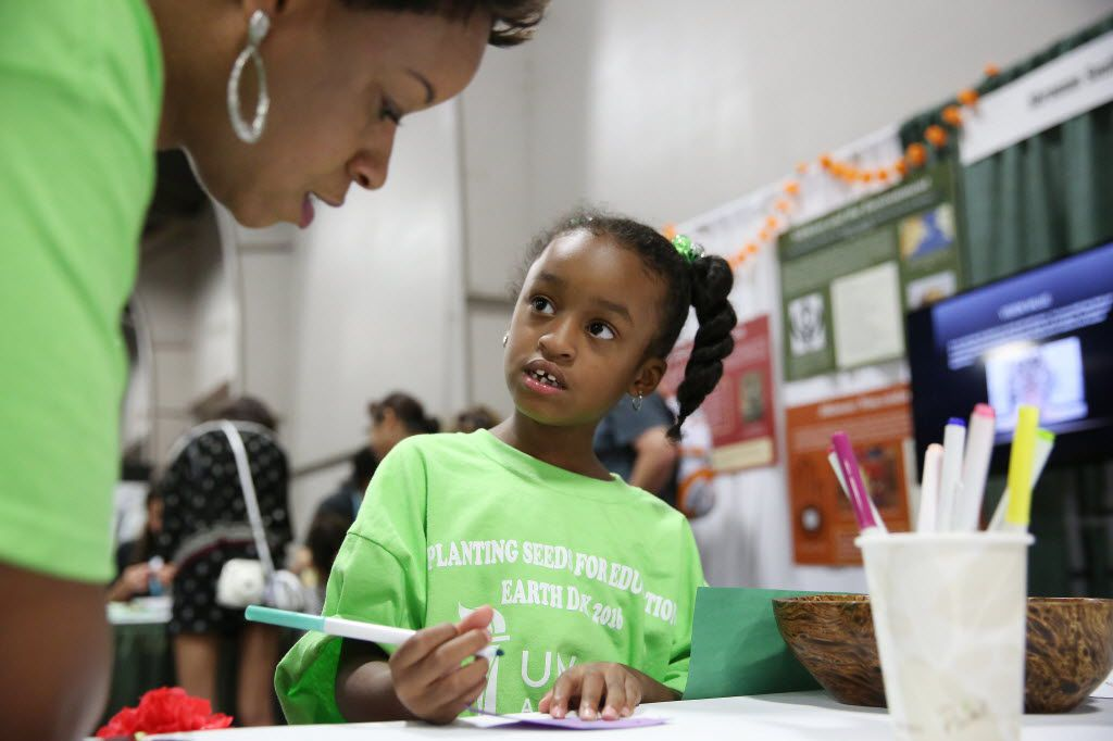 """Cortney Smith, of Dallas, watches as her daughter, Jordyn Smith, 5, writes """"I will not litter"""" on a eco-pledge program leaf at the exhibition space for the Shraman South Asian Museum during Earth Day Texas and Fair Park in Dallas Saturday April 23, 2016. The event had 771 environmental nonprofit groups, government agencies, business and academic institutions. The three-day event includes speakers, student field trips, and the E Day conference. (Andy Jacobsohn/The Dallas Morning News)"""
