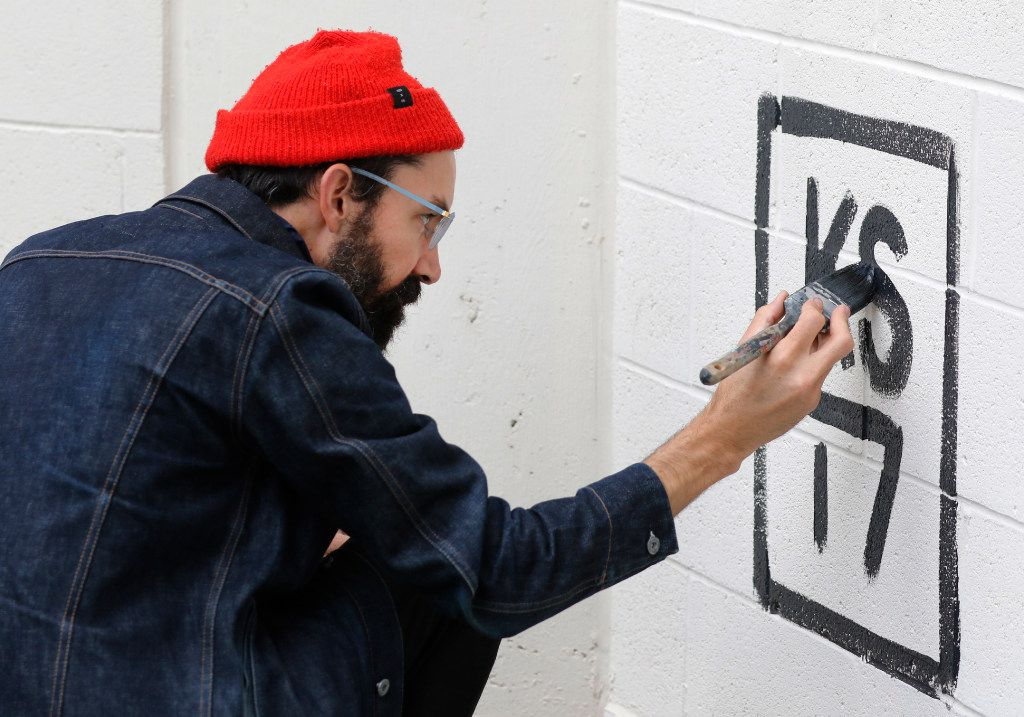 Muralist Kyle Steed signs his name to a mural at Plaza of the Americas.