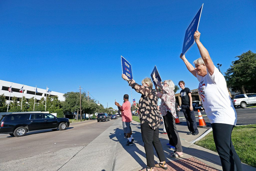 Trump supporters Linda Liebman (right), Toni Wirth (left) and Honey Lanham Dodge hold signs as the motorcade carrying Republican presidential candidate Donald Trump leaves the Lincoln Centre after a fundraising event in Dallas, Tuesday, Oct. 11, 2016.