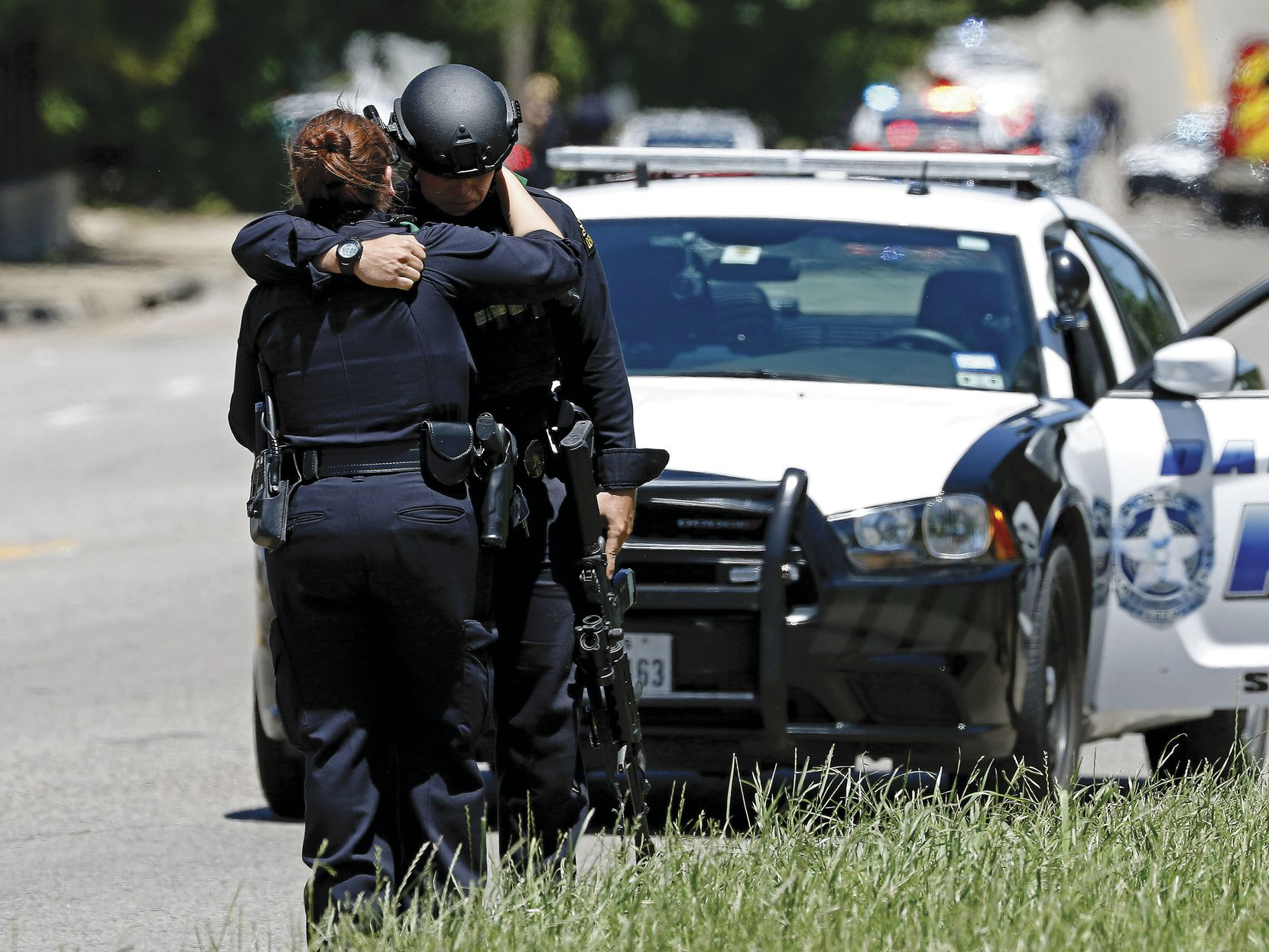 Two Dallas police officers comfort each other at a shooting scene on Dolphin Road where a Dallas Fire-Rescue paramedic nearly lost his life to a suicidal gunman. The paramedic, William An, spent almost a month in the hospital.