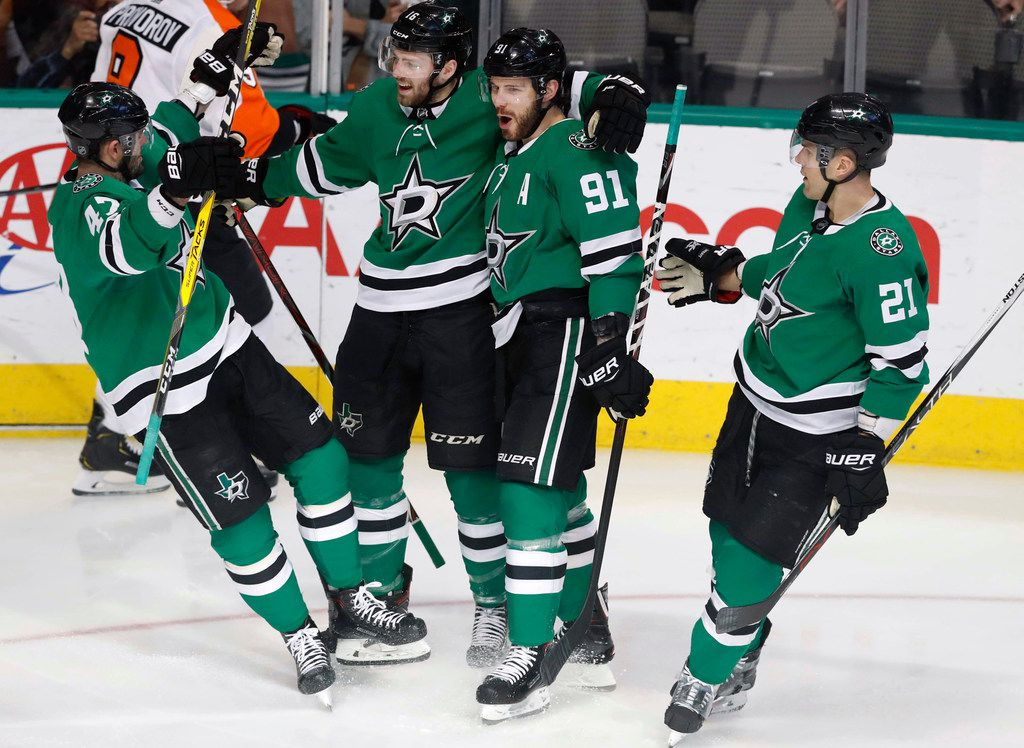 Dallas Stars center Jason Dickinson, second from left, celebrates his goal with teammates Tyler Seguin (91), Alexander Radulov (47) and Ben Lovejoy (21) during the first period of an NHL hockey game against the Philadelphia Flyers in Dallas, Tuesday, April 2, 2019. (AP Photo/LM Otero)