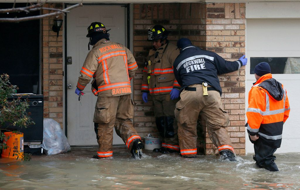 Rockwall firefighters enter a flooded house on Lakeside Drive in Rockwall, Texas, Thursday, Feb. 22, 2018.