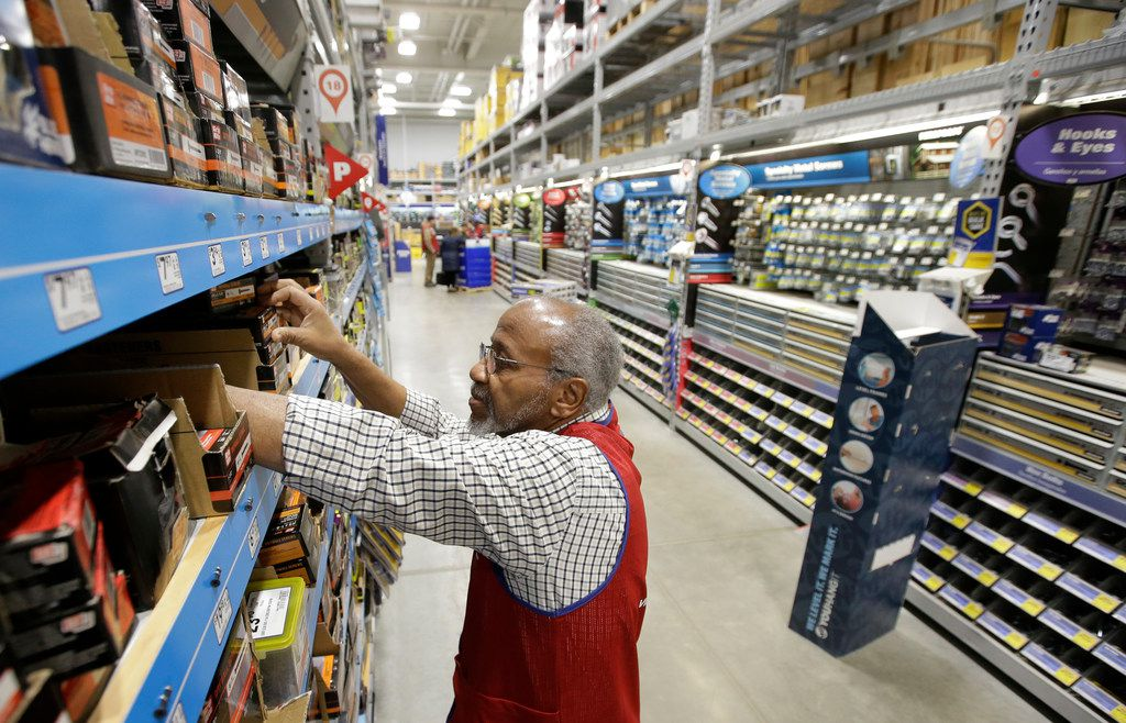 In this 2018 file photo, sales associate Larry Wardford of Holliston, Mass., puts items on shelves at a Lowe's retail home improvement and appliance store in Framingham, Mass.