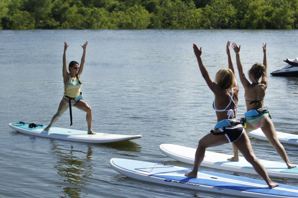 Instructor Jenn Bodnar leads a stand-up paddleboard yoga class at DFW Surf on Lake Lewisville.