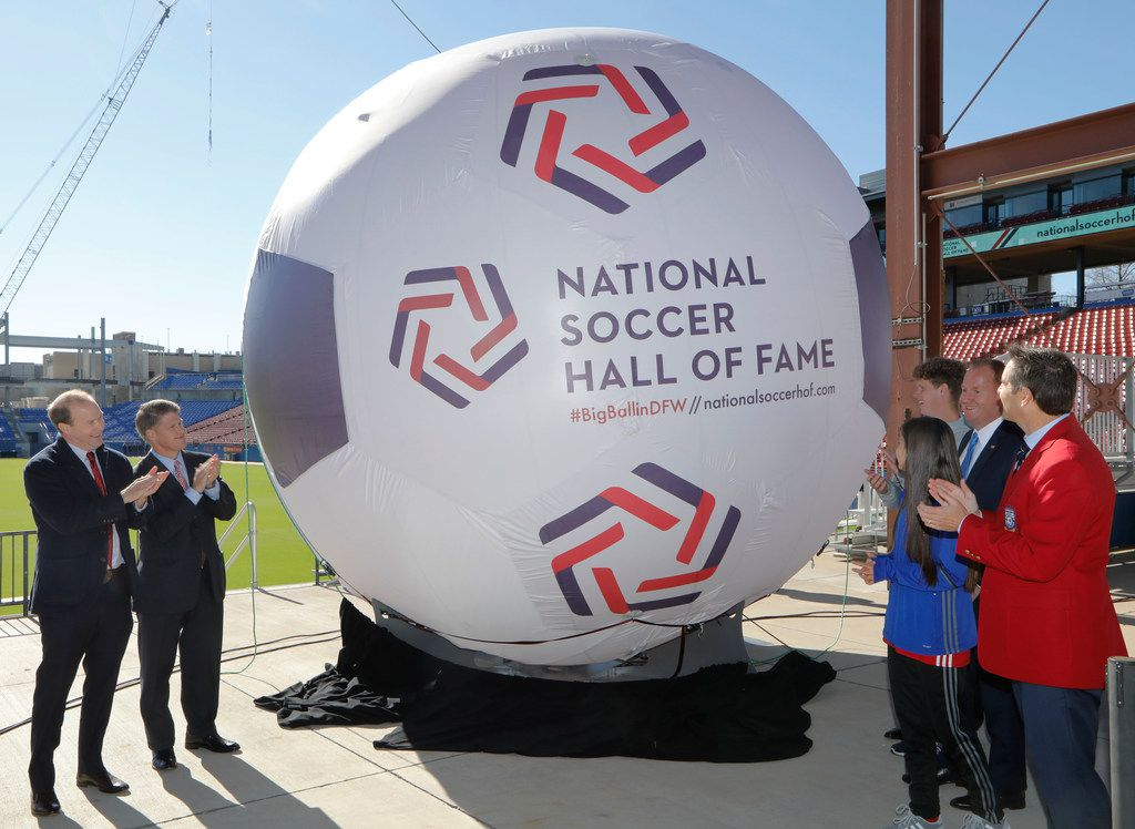 From left: FC Dallas president Dan Hunt, FC Dallas chairman Clark Hunt, Frisco Mayor Jeff Cheney (blue tie), and John Harkes (red coat), a member of the 2005 National Soccer Hall of Fame class were among those unveiling the new logo for the National Soccer Hall of Fame on Tuesday.