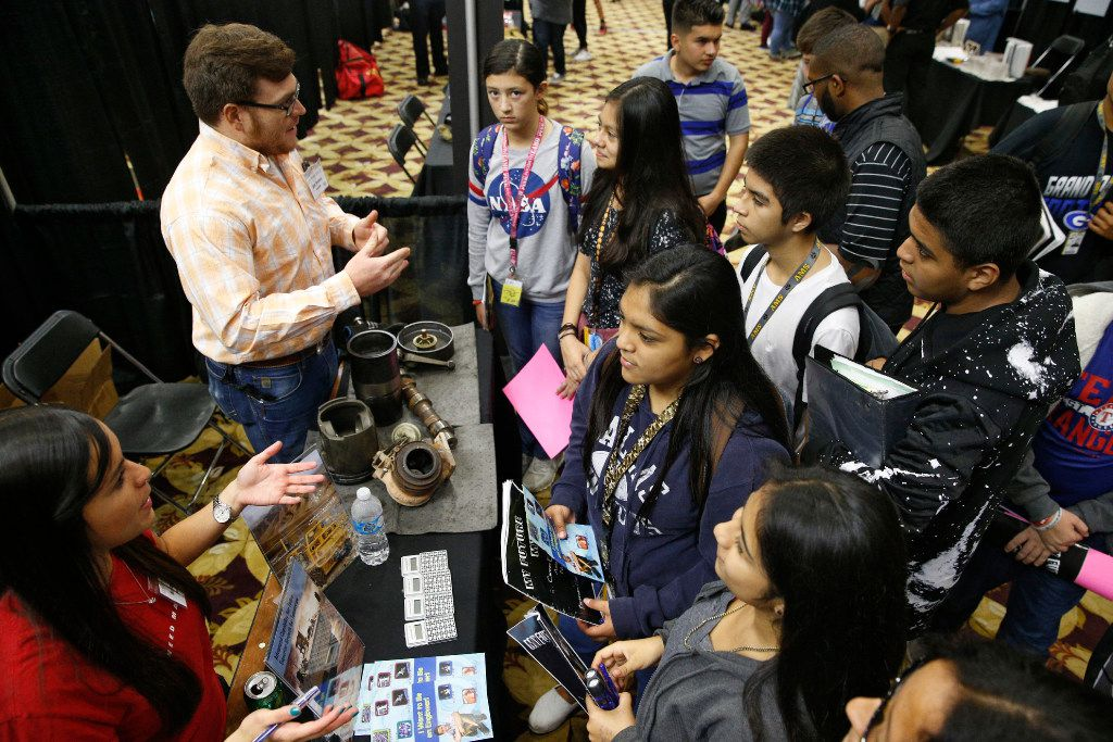 Alex Perales (top left) and Natalia Espino (bottom left) talk about engineering to students from John Adams Middle School as a part of the My Future My Way exhibit in Grand Prairie.