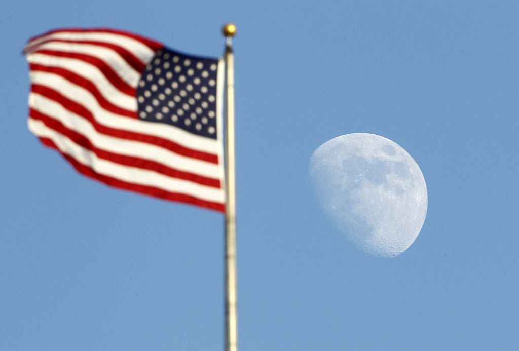 The moon rises past the U.S. flag at the Rangers Ballpark in Arlington, Saturday, July  28, 2012.