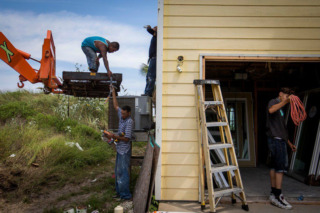 Workers replace windows on a home on South 12th Street that's still vacant nearly a year after Hurricane Harvey devastated the Texas Gulf Coast city of Port Aransas.