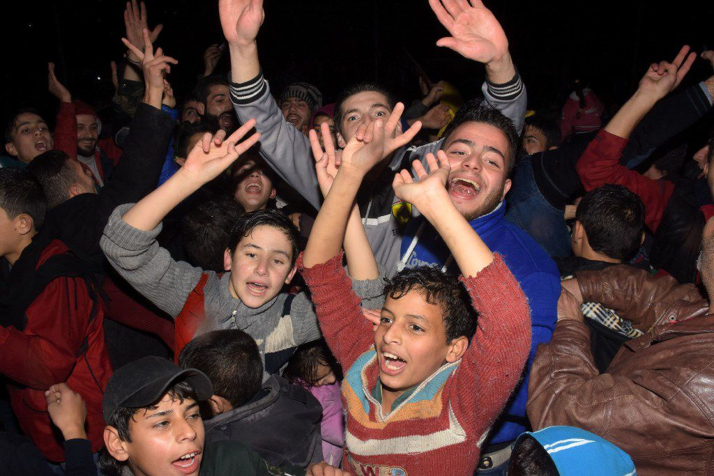 Syrians celebrate on December 12, 2016 in the government-held Mogambo neighbourhood of the northern Syrian city of Aleppo, after rebel fighters retreated into a small pocket of their former bastion in the face of new army advances.