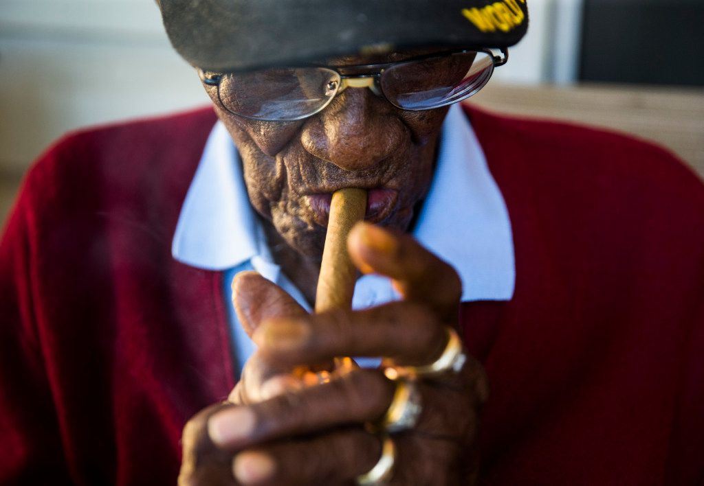Richard Overton, 111, lights up a cigar on his front porch on May 25 on Richard Overton Avenue in Austin.