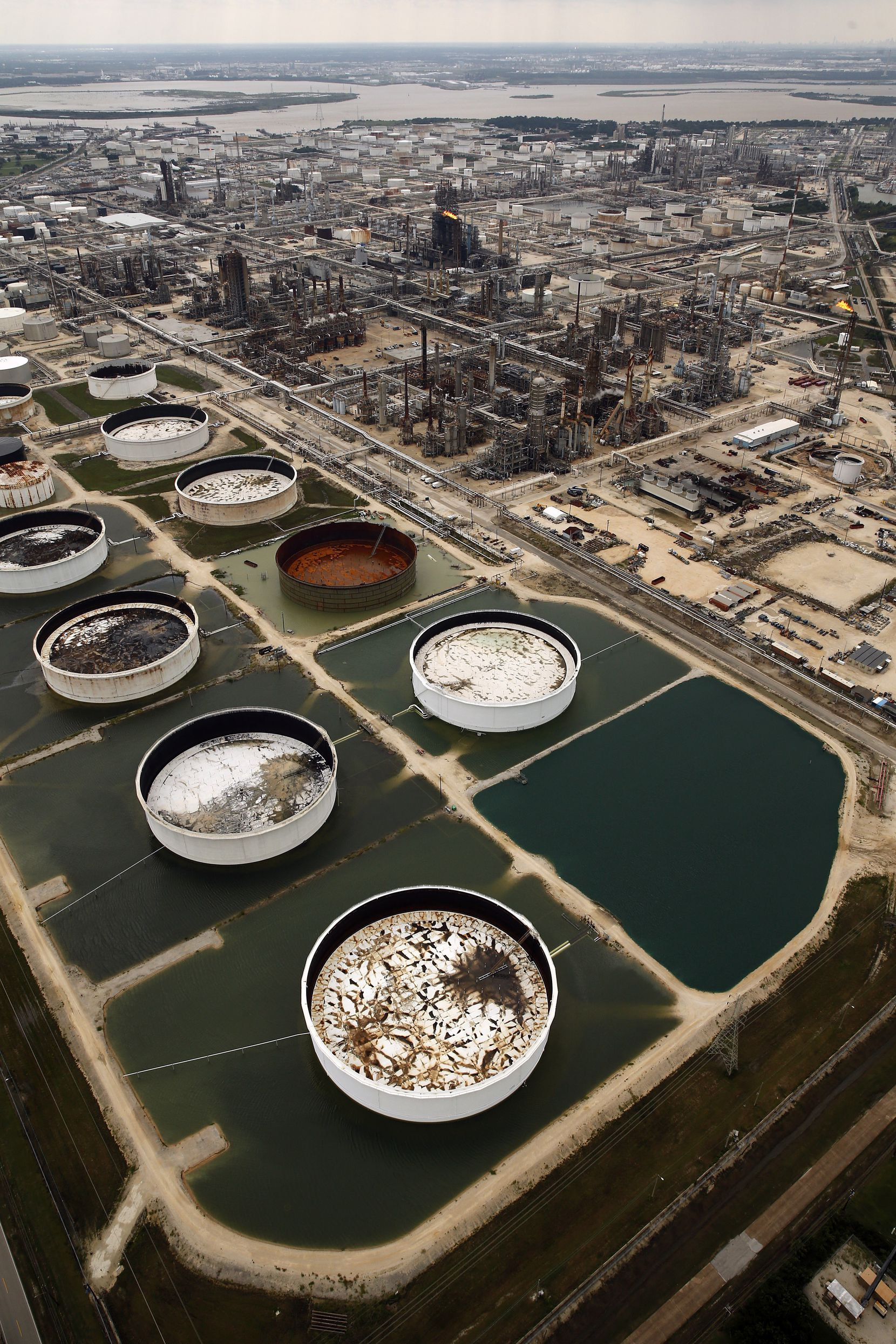 Large storage tanks situated in retention ponds are surrounded by rainwater left behind by Hurricane Harvey at ExxonMobil's refinery in Baytown, Texas, Wednesday, August 30, 2017.