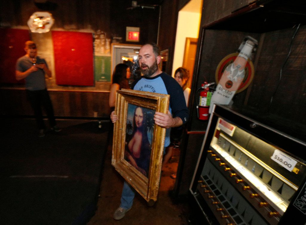 Fellow bar owner Mark Melton walked out with a topless Mona Lisa poster after purchasing it from the Elbow Room's owners for $2,000 during the last hours of operation early Sunday. (Nathan Hunsinger/Staff Photographer)