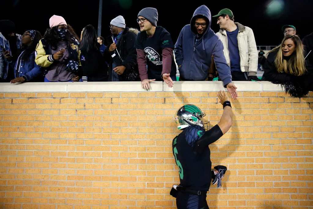 Using his non-injured hand, North Texas Mean Green quarterback Mason Fine (6) slaps hands with fans following their win over Florida Atlantic at Apogee Stadium in Denton, Texas, Thursday, November 15, 2018. Fine left the game and got stitches in his hand following a third quarter injury. (Tom Fox/The Dallas Morning News)
